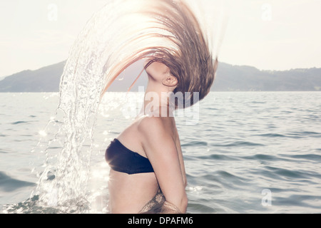 Young woman in sea throwing head back - Stock Photo
