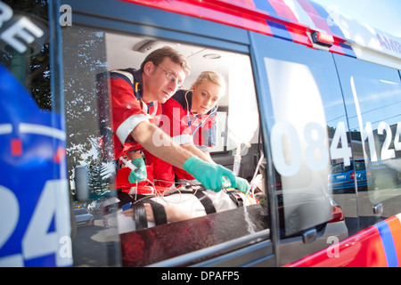 Paramedics monitoring patient in ambulance - Stock Photo