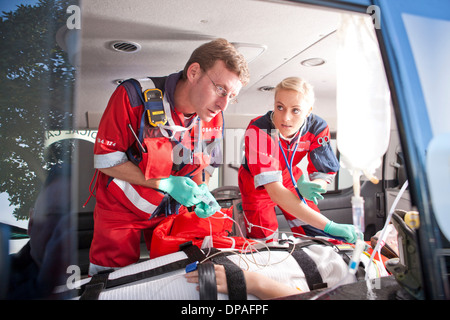 Paramedics working on patient in ambulance - Stock Photo