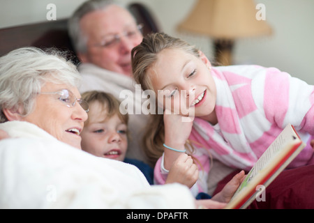 Grandparents and grandchildren reading storybook in bed - Stock Photo