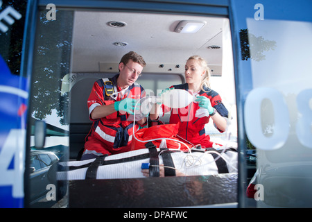 Paramedics ventilating patient in ambulance - Stock Photo