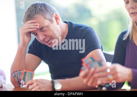 Mature male playing cards with family - Stock Photo