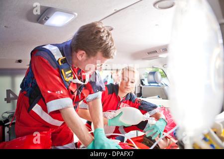 Paramedics giving patient heart massage in ambulance - Stock Photo