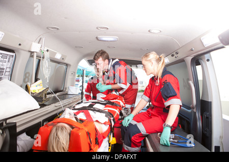Paramedics in ambulance working with patient - Stock Photo