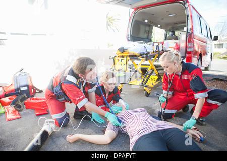 Paramedics tending patient lying on road - Stock Photo