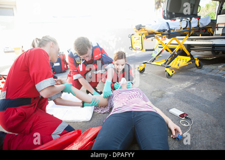 Three paramedics tending patient on road - Stock Photo