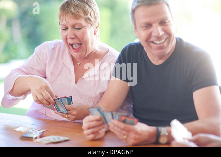 Mature male playing cards with sister - Stock Photo