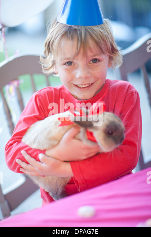 Young birthday boy hugging his rabbit - Stock Photo