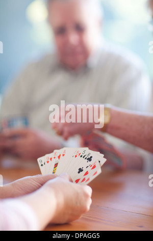 Senior male playing cards with family - Stock Photo