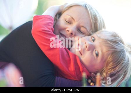 Young birthday boy hugging his mother - Stock Photo