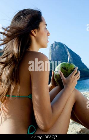 Young woman holding coconut drink, Rio de Janeiro, Brazil - Stock Photo