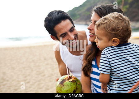 Family on beach with coconut drink