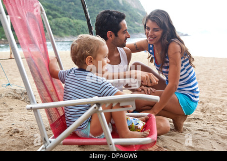 Family on beach, boy sitting on chair - Stock Photo