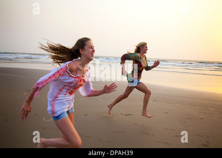 Mother and daughter running on beach - Stock Photo