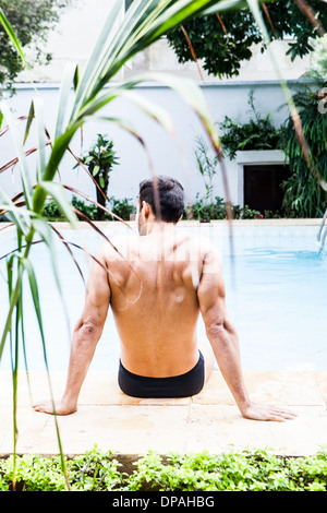 Man sitting at poolside - Stock Photo