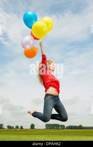 Woman jumping with balloons - Stock Photo
