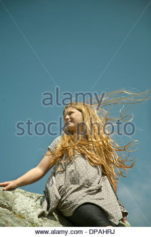Teenage girl with long red hair sitting on rocks in wind - Stock Photo