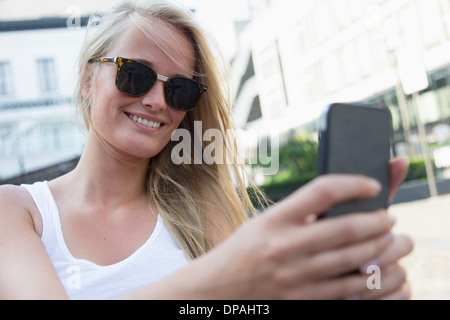 Young woman using cellular phone - Stock Photo