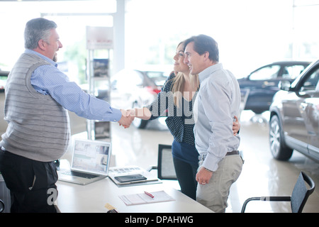 Car salesman and couple shaking hands in car showroom
