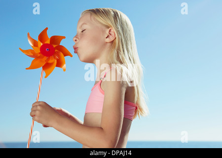 Girl blowing at toy windmill - Stock Photo
