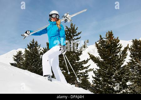 Woman carrying skis uphill, Obergurgl, Austria - Stock Photo