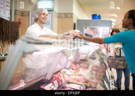 Young male sales assistant serving customer at counter - Stock Photo