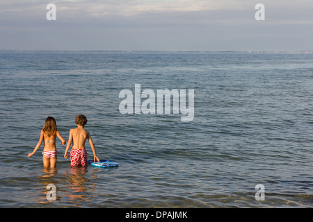 Brother and sister paddling in sea - Stock Photo