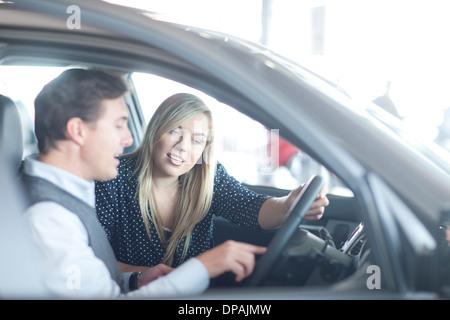 Car salesman advising young woman in car showroom - Stock Photo