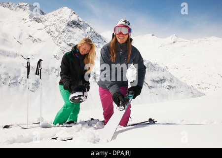 Two woman in snow with skis, Obergurgl, Austria - Stock Photo