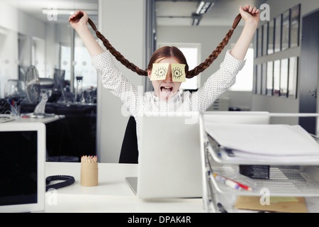 Girl in office with adhesive notes covering eyes holding plaits - Stock Photo
