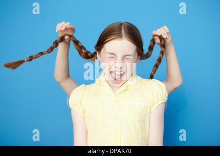 Girl wearing yellow school dress, boy behind pulling her plaits - Stock Photo