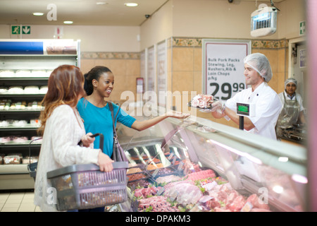 Young male sales assistant serving female customers - Stock Photo