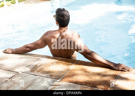 Man in swimming pool leaning with arms outstretched - Stock Photo