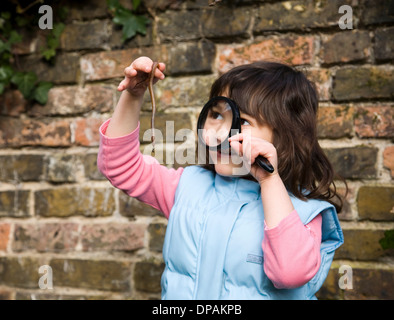 Girl looking at worm with magnifying glass - Stock Photo