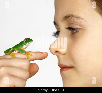 Girl with a red-eyed tree frog on her finger - Stock Photo