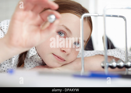 Girl playing with newton's cradle on desk - Stock Photo