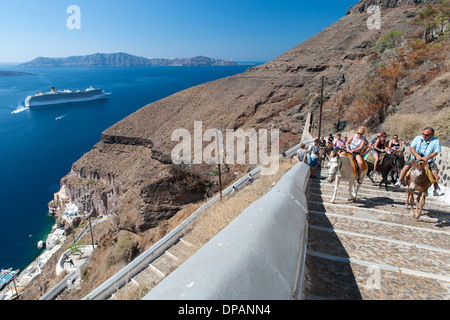 Tourists riding donkeys up the steps leading from the old port to the village of Fira on the Greek island of Santorini. - Stock Photo