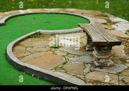 Outdoor green mini golf with bench near it - Stock Photo