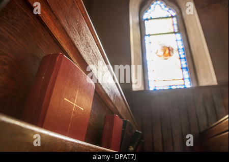 Church pew and stained glass window light - Stock Photo