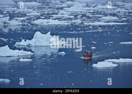 Fishing boat among icebergs in Disko Bay, Ilulissat, West Greenland - Stock Photo