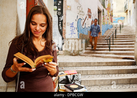 Portugal, Lisboa, Baixa, Rua do Madalena, young woman with book standing in front of antiquarian bookshop - Stock Photo