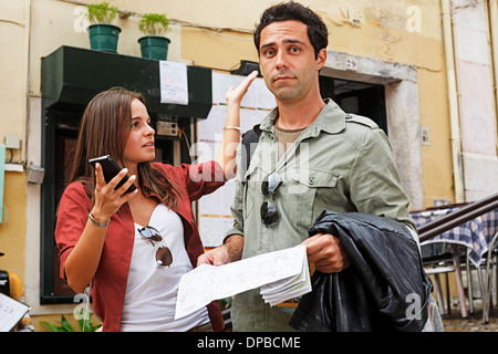 Portugal, Lisboa, Carmo, Calcada du Duque, young couple with city map and smart phone trying to orientate - Stock Photo