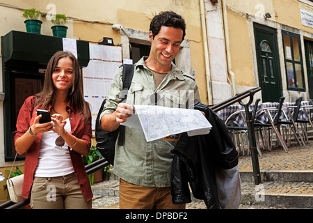 Portugal, Lisboa, Carmo, Calcada du Duque, young couple with city map trying to orientate - Stock Photo