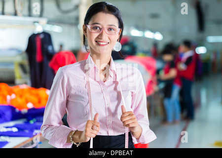 Female Indonesian tailor, dressmaker or designer standing proudly in an Asian textile factory, it is her workplace - Stock Photo