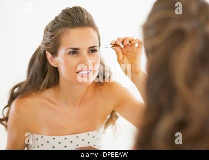 Happy young woman tweezing eyebrows - Stock Photo