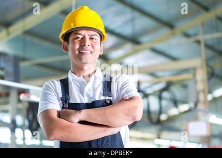 Indonesian Worker or production manager standing proudly in a Asian textile factory or industrial plant, it is his - Stock Photo