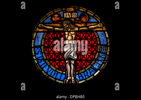 round stained glass window at the lutheran church of sessenheim showing jesus at the cross and a text :_it is fulfilled - Stock Photo