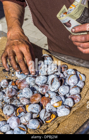 roasted chestnuts are being filled in a bag made of newespaper, aljustrel, alentejo, portugal - Stock Photo