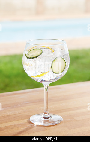 Cucumber gin and tonic cocktail on poolside bar - Stock Photo