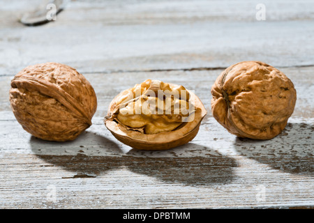 Two whole and a half of a walnut (Juglans regia) on wooden table, close-up - Stock Photo